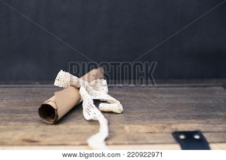 Scrolled brown papyrus with a beautiful ribbon for valentine message with simple black background