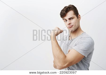 Young positive handsome muscular man wears gray t-shirt, shows biceps after training in gym, demonstrating how strong he is, isolated against gray background. Mocking, making faces caucasian male boasts of his strength, demonstrating his strong arm