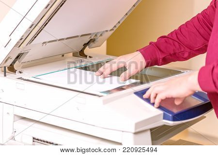 Man putting paper sheet on printer for scanning. Office work concept