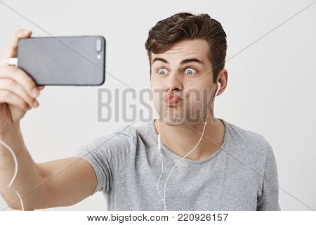 Gloomy caucasian male student frowns face, holding smart phone in his hand, looking at camera with popped eyes, pouting lips, making faces, posing for selfie. Young good-looking guy having fun and mocking
