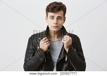 Portrait of handsome attractive male model with appealing blue eyes and trendy haircut in stylish black leather jacket, looks confidently at camera. Good-looking caucasian guy posing against gray background.