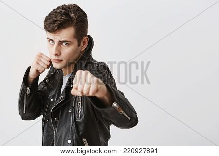 Fierce and confident stylish european male model in black leather jacket with trendy haircut holding fists in front of him as if ready for fight or any challenge, pursuing lips, having determined expression on his face