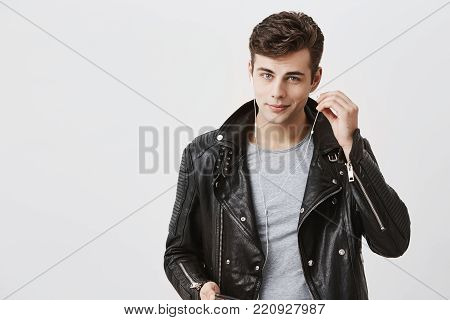 Handsome positive man in trendy black leather jacket with faint smile, listens music in earphones. Young delightful caucasian male enjoys pleasant melodies alone, wearing white earphones, looking at camera with his blue eyes.