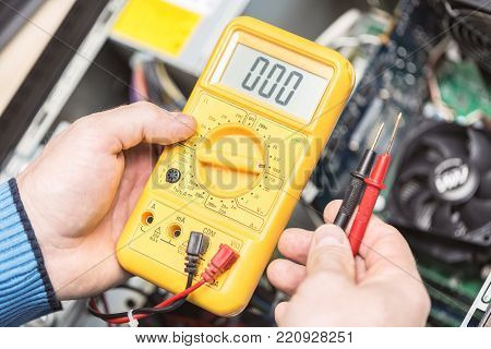 Technician hands holding voltmeter above computer motherboard. Repair of computers concept. Toned with selective focus.