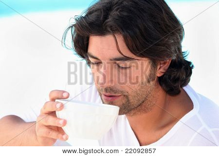 Man drinking coffee by swimming pool