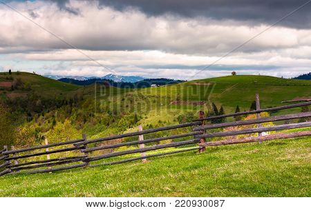 wooden fence on a grassy slope of Carpathian alps. beautiful view of rural fields on hills. mountain ridge with snowy tops in the distance. lovely countryside landscape in springtime