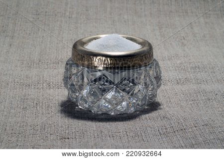 vintage faceted saltcellar made of crystal with a tarnished brass rim, full of salt, closeup, on a coarse linen tablecloth