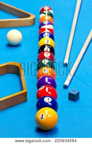 Billiard pool game balls lined up on billiard table with blue cloth with cues, racks, and chalk
