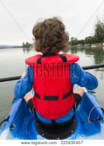 Smartphone image young boy in red life jacket kayaking from behind