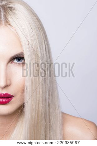 A half of face. Beautiful close up shot of a scandinavian looking cold blonde girl with blue eyes and red lips.