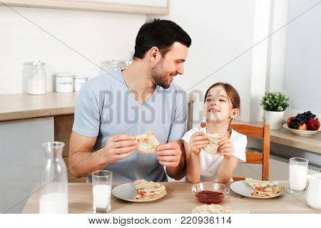 Affectionate pleasant looking father and his little daughter eat tasty morning meal at kitchen, communicate with each other. Dad feeds small child with pancakes and milk. Having breakfast together