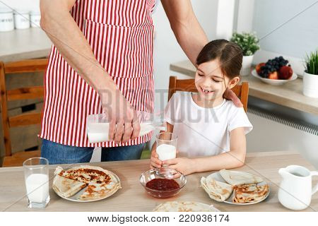 Cropped image of careful father wears apron, pours fresh milk in glass for his daughter, bakes delicious pancakes, prepares breakfast for child, being together at kitchen. Family, food, children