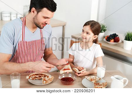 Photo of friendly family have breakfast together. Bearded man spreads jam on thin fried pancake, sits with her little daughter at kitchen, going to have sweet delicious dessert. Parenthood concept