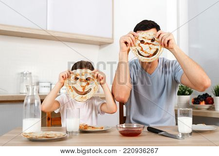 Funny pretty daughter and father make faces with pancakes, make fun together at kitchen during weekends, enjoy delicious flannel cake, foolish. Family, parenthood, food and cookery concept