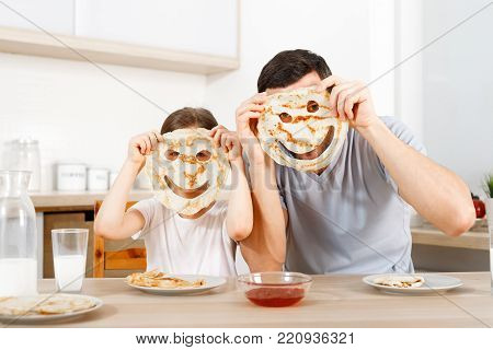Positive friendly daughter and father make funny faces from pancakes, looks through handmade eyes, sit at kitchen, have breakfast, wait for mother. People, relationship, culinary, family concpet