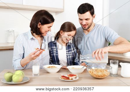 Happy young parents and their lovely daughter sit together at kitchen table, eat flakes, have healthy breakfast, enjoy good morning, have friendly relationship. Family and eatting concept