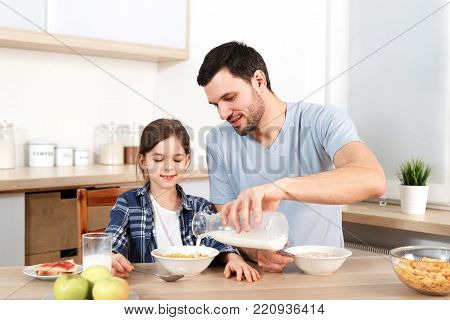 Young handsome father pours milk in bowl with flakes, prepares breakfast for small child, sit together at kitchen, have healthy food, enjoy togetherness. Friendly family being at home, eat