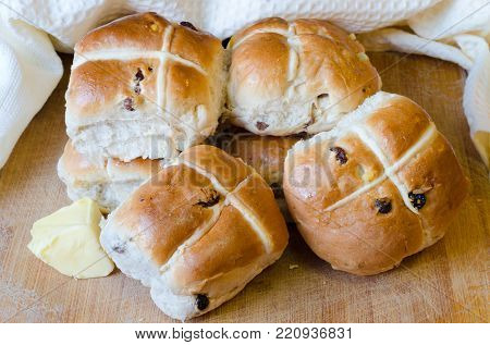 A pile of hot cross buns on a wooden board with a knob of butter.