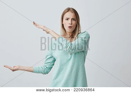 Pretty cute blonde female wearing casual clothes showing something big in size with hands while gesturing, frowning her brows, pouting her lips. Blonde European woman demonstrating size of something posing at camera