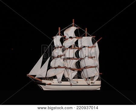 Wooden sail boat with ropes cloth sails at full mast isolated on a black background
