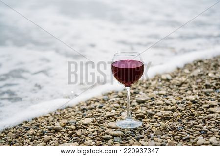 A glass of red wine on the pebble beach at the sea coast. Vacation pleasure concept poster