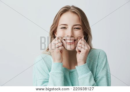 Charming broadly smiling with perfect teeth young European woman with blonde long hair wearing light blue sweater, pinching her cheeks, mocking, having good mood and fun. face expressions and emotions
