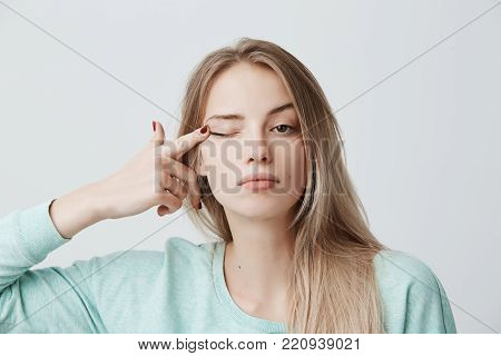 Human face expressions.Thoughtful young beautiful female with blonde dyed straight hair in light blue long-sleeved sweater touching with finger eye, looking at camera with serious and calm expression.