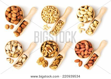 Set of nuts in a wooden bowl and scoop. Hazelnuts, pistachios, cashews, pine nuts, walnuts and peanuts on a white background.