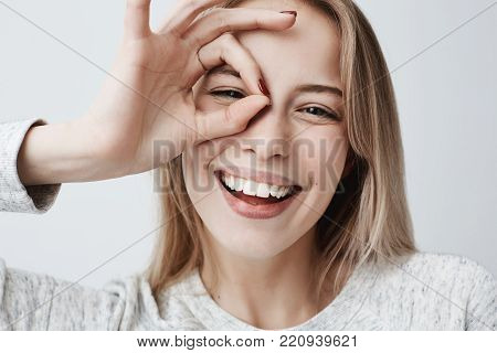 Close up portrait of young beautiful joyful blonde Caucasian female smiling, demonstrating white teeth, and looking at the camera through her fingers in okay gesture. Human face expressions and emotions, body language