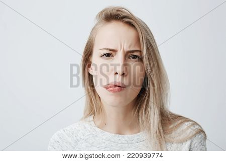 Negative human reaction, feelings and attitude. Close-up portrait of disgusted squeamish blonde woman in casual wear grimacing, sticking out her tongue, feeling nauseous because of bad smell or stink
