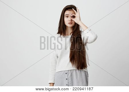 Cheerful excited teenage girl with dark long straight hair showing Ok gesture with hand, enjoying her carefree happy life, dressed casually. Body language and gestures concept