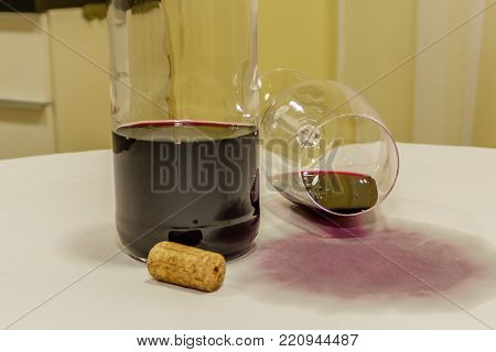 Red wine spilled from glass over white tablecloth with bottle and cork
