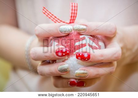 Christmas nail art manicure, winter holiday style bright manicure with gems and snowflakes. Beauty hands. Trendy Stylish Colorful Nails, Nail polish