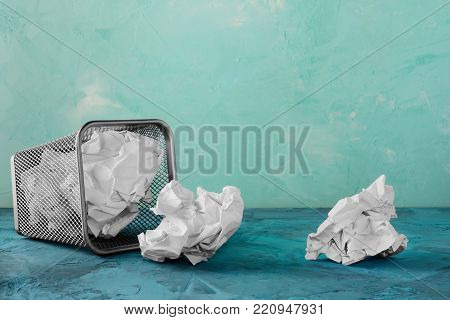 A fallen trash can for paper. Scattered paper lumps. Beautiful unusual turquoise background with place for text. Empty bin.