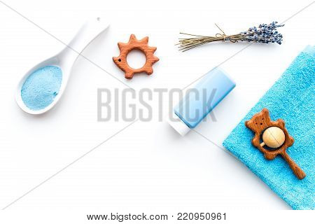 Hypoallergenic bath cosmetics for kids. Bottle, spa salt, towel and toy on white background top view.