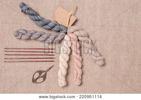 Pastel colors hank of yarn, scissors, rough woolen yarn and wooden knitting needles on canvas background.