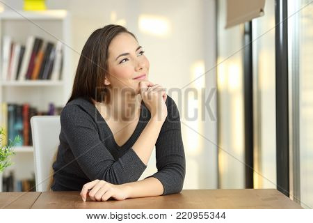 Portrait of a dreamer woman wondering in the living room at home