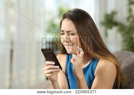 Hopeful girl crossing fingers holding a smartphone waiting for news sitting on a couch in the living room at home