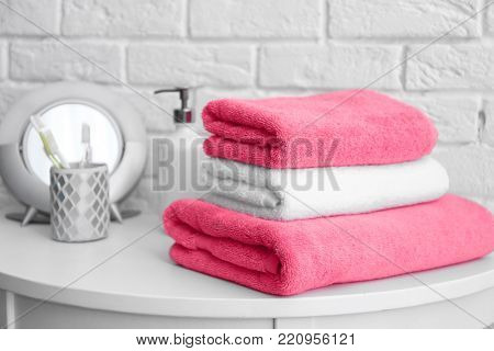 Stack of clean towels and toiletries on table near white brick wall