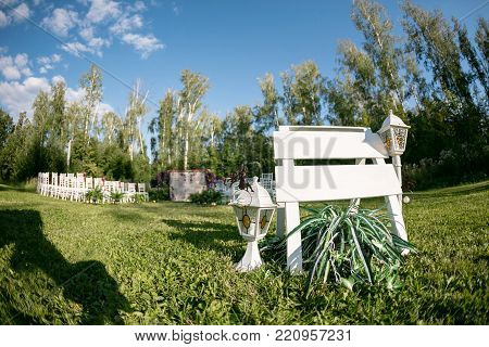 Beautiful setting for outdoors wedding ceremony waiting for bride and groom and guests. White chairs decorated with flowers, are in the zone of the wedding ceremony in a forest.