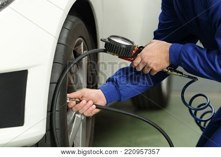 Close up of a car mechanic hands checking tire air with a pressure gauge
