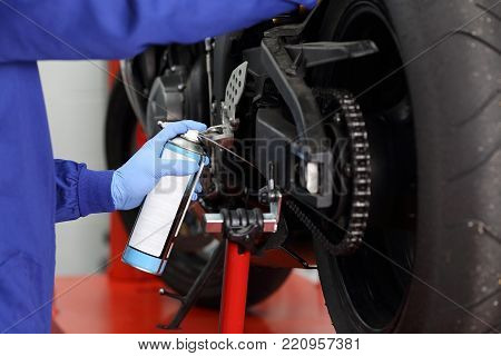 Close up of a motorcycle mechanic hands wearing latex gloves oiling a motorcycle chain in a workshop