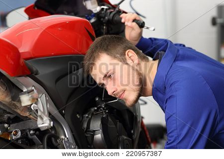 Motorcycle mechanic listening engine noise to find failures in a mechanical workshop