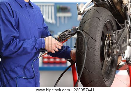 Close up of a motorbike mechanic hand checking tires air with a pressure gauge in a workshop