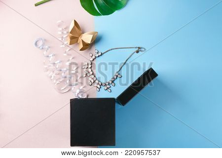 Opened gift box, necklace and streamers on color background, top view