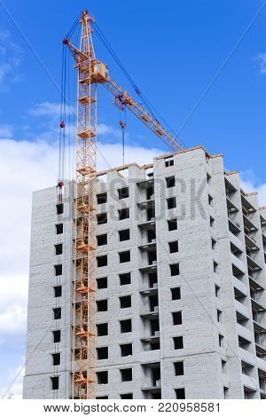 Cranes over unfinished buildings on construction site at a bright sunny day.