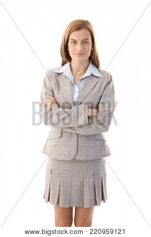 Confident young businesswoman standing arms crossed, wearing mini skirt.