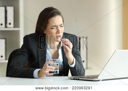 Ill businesswoman complaining and taking pill working sitting in a desktop at office