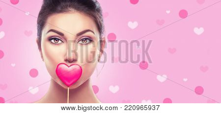 Beauty surprised Young fashion model Girl with Valentine Heart shaped cookie in hand. Love. Beautiful young woman with red heart on lips, advertising  Valentines Day gift. Pink hearts background.