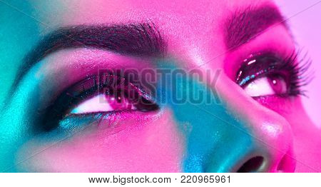 High Fashion model woman in colorful bright lights posing in studio, portrait of beautiful sexy girl with trendy eyes make-up close-up. Art design, colorful make up. Over purplel vivid background.